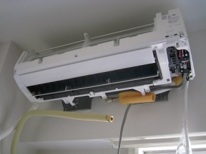 室内機を据付板に引っかけてパイプを接続