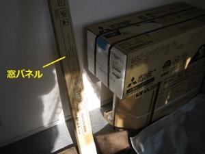 梱包されている新品のエアコンと窓パネル