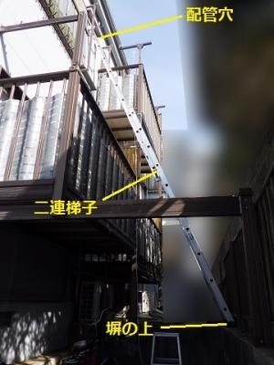 二連梯子を塀の上から掛けてエアコンの取り外し工事
