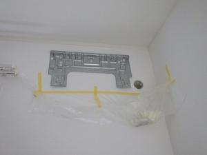 据付板を仮付けして石膏ボードに配管用の穴を開ける